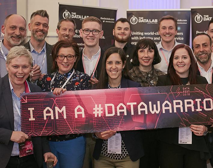 The Data Lab team holding I am a #DataWarrior banner
