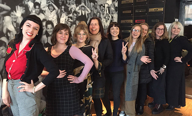 Lineup of business women smiling and posing