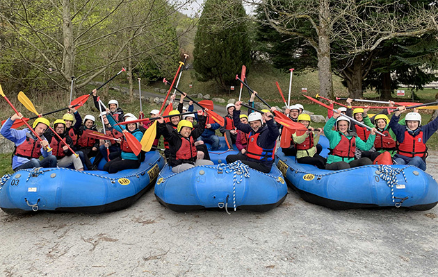The Data Lab team photo in 3 river rafting boats, wearing helmets, waving paddles