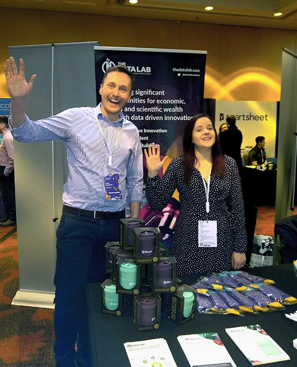 Team members waving at DataTalent stand